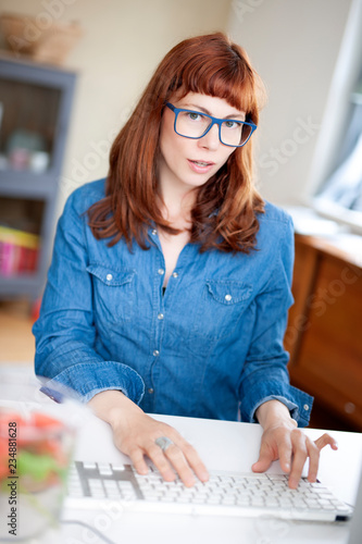 fototapeta na ścianę Lady with red Hair and blues glasses in home office