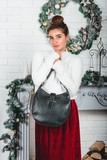 black fashionable handbag in a hands of gorgeous young female in a red skirt and white pullover on a christmas decorated wall background