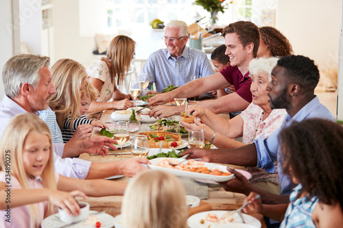 Group Of Multi-Generation Family And Friends Sitting Around Table And Enjoying Meal - 234890275