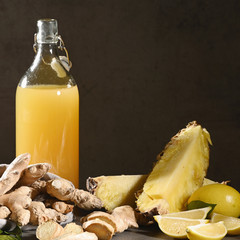 Bottle of homemade pineapple juice with ginger, lemon and ingredients. Squared.