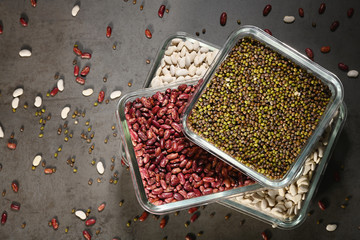 White beans, red beans mung bean in glass bowls on a dark background. Eco friendly, plastic free items.