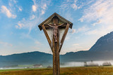 wooden crucifix in the tyrolean alps in morning time