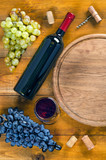 Bottle and glass with wine, grapes, corkscrew, cork on wooden background.