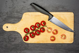 Slicing cherry tomatoes. recipe step by step farfalle with arugula leaves on chopping board flatlay on grey stone - 234934065