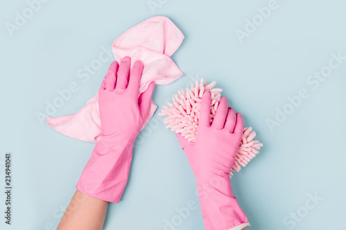 Leinwandbild Motiv Female hands cleaning on blue background. Cleaning or housekeeping concept background. Copy space.  Flat lay, Top view.