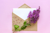 Branch of lilac on craft envelope with white empty paper card for text, pink background. Greeting card Flat Lay Mock up Concept hello spring - 234947404