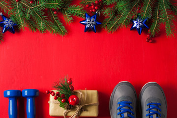Christmas sport composition dumbbells sneakers branches concept healthy lifestyle