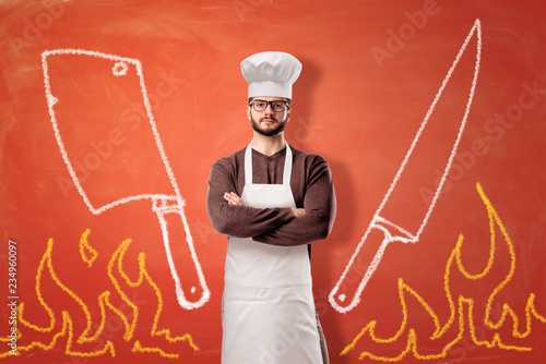 Leinwanddruck Bild A bright orange background with drawn flames, a cleaver, a knife and a serious male cook standing in the center.