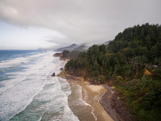 Aerial View of the Oregon Coastline. Waves roll in between Arch Cape and Cannon Beach on the Pacific Ocean in the Pacific Northwest. Haystack Rock can be seen in the distance. © LoweStock