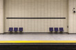 Two sets of purple chairs attached to tiled wall