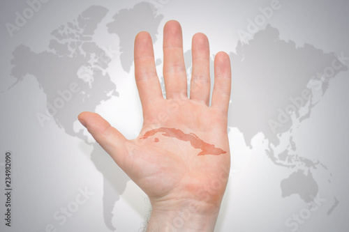 hand with map of cuba on the gray world map background.