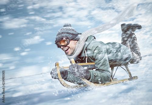 Leinwanddruck Bild Mann in voller Fahrt beim Rodeln im Schnee