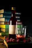 Bottle and glass with craft raspberries alchol drink with berries around on background with books.