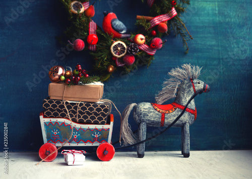 Leinwandbild Motiv christmas ,new year,birthday card/ wooden toy horse with sledges ,gifts and christmas wreath