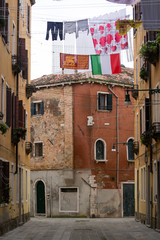 A not touristy spot in Venice, italy, november 2018. The beauty of this city is also in the not famous areas where residents are local, exposed here there are two flags , the italian and venetian
