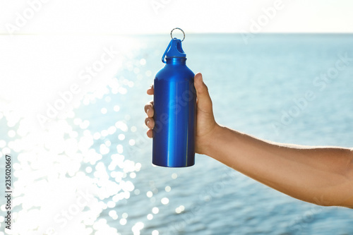 Leinwandbild Motiv Young sporty man holding water bottle near river on sunny day. Space for text