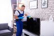 Male Janitor Cleaning Television