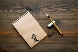 Chinese traditional calligraphy concept. Asian hieroglyph love in craft paper notebook near special writting pen on dark wooden background top view