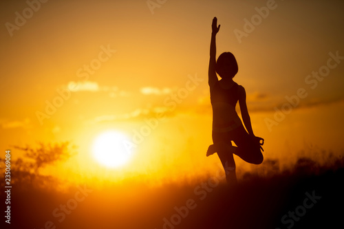 fototapeta na ścianę woman standing in yoga pose with sunset background