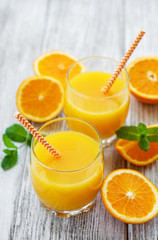 Glasses of juice and orange fruits