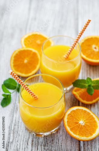 Glasses of juice and orange fruits - 235078492