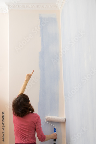 Woman applying paint on wall