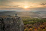 Sunset from the top / Silhouette of a woman on the top of a rock enjoys the view of sunset over an autumn forest © jessivanova