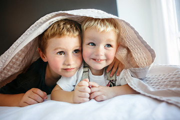 Brothers play together.Two boys brothers lie under a blanket in bed.