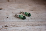 Handmade earrings made of malachite and hematite on a light background.