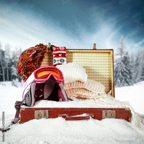 Leinwanddruck Bild Retro old suitcase in snow and winter landscape