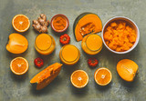 Orange smoothie ingredients background for cold season with  pumpkin, orange fruits, ginger, turmeric and persimmon fruits , top view. Healthy vitamin C rich,  mood and energy smoothie drinks