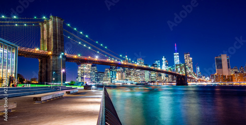 fototapeta na ścianę Beautiful Brooklyn Bridge and the illuminated Skyline of Manhattan in the evening with blue sky and smooth water surface. Picture taken from the Brooklyn district, New York, USA.