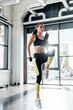 Leinwanddruck Bild - beautiful fit sportswoman jumping and warming up at gym