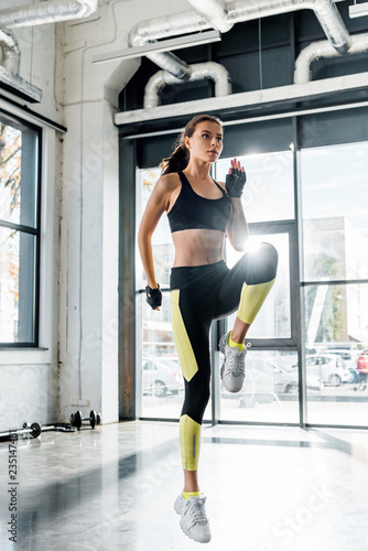 Leinwanddruck Bild beautiful fit sportswoman jumping and warming up at gym