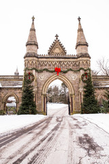 Old vintage cemetery gates architecture with snow and Christmas wreath from Forest Hills Cemetery in Boston area