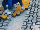 Paving stone worker is putting down pavers during a construction of a city street onto sheet nonwoven bedding sand and fitting them into place. - 235171823