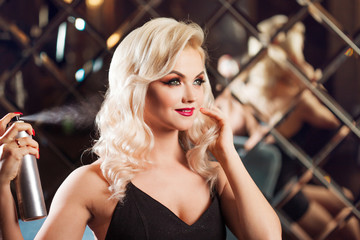 Beautiful young blonde doing her hair. Glamorous make-up. attractive young woman uses hairspray.