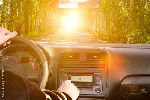 the driver behind the wheel of the car, the road with trees on the roadside. journey, trip.