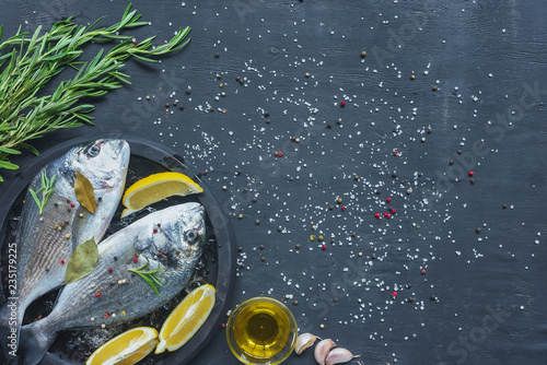 Leinwandbild Motiv view from above of raw fish with lemon, bay leaves and rosemary in tray on black table covered by salt and pepper