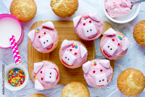 fototapeta na ścianę Pig cupcakes - homemade cakes shaped funny piggies decorated with pink cream and marshmallow, new year 2019 or easter treats for kids