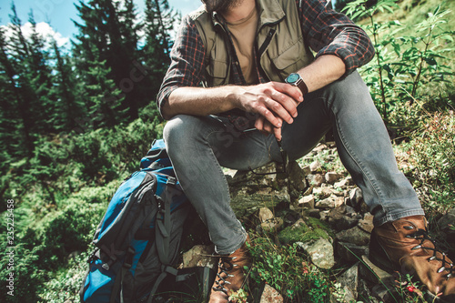 Take a breath in journey and adventure. Close up full length portrait of young man sitting on stone of sunny green hill to have rest - 235225458