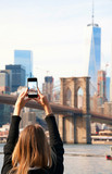 Young woman taking photo with smartphone at Brooklyn Bridge, New York City