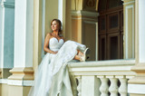Young woman in a white wedding dress on the streets of European cities . Happy young girl on wedding day