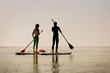 Leinwandbild Motiv Silhouette of young happy couple doing paddle yoga