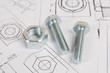 Technical drawings of bolt and nut. Engineering, technology and metalworking. Metal bolt and nut on printed drawings background.