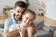 Leinwandbild Motiv Portrait of happy millennial couple hug looking at camera, smiling husband hold in arms beloved young wife posing in living room, headshot of excited first time buyers make family picture in new home