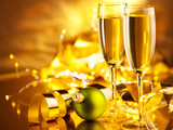 Christmas scene. Holiday champagne over golden glow background. Christmas and New Year celebration. Two flutes with sparkling wine over holiday bokeh blinking background - 235310863