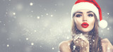 Christmas winter fashion girl on holiday blurred winter background. Beautiful New Year and Xmas holiday makeup. Beauty model woman in Santa's hat blowing snow in her hand - 235311001