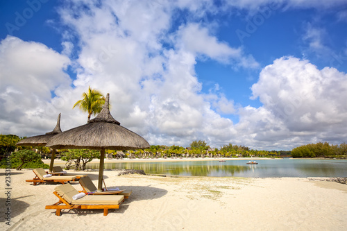 Sand beach with lounge chairs and umbrellas in Mauritius Island