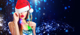Christmas sexy woman. Beauty model girl in Santa's hat with glass of champagne in her hand celebrating on blinking holiday winter wide background - 235320863